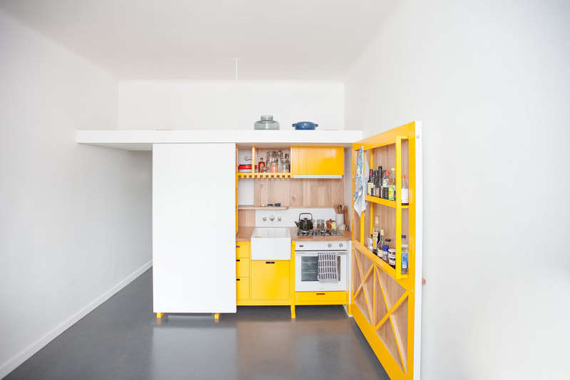 This chic mini kitchen was built for a studio apartment and features bold yellow cabinets and lots of storage space