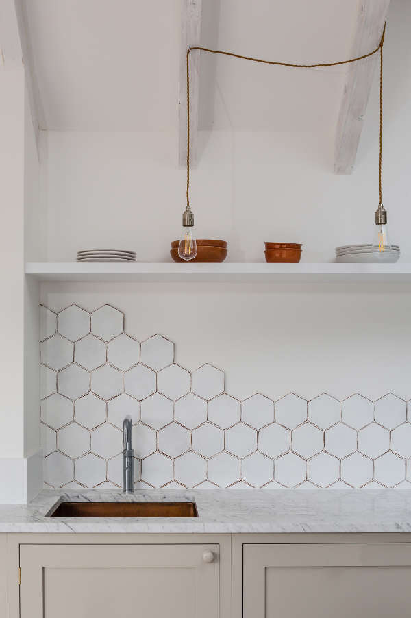 The dove grey cabinets are made more eye catchy with white marble countertops and a white hex tile backsplash