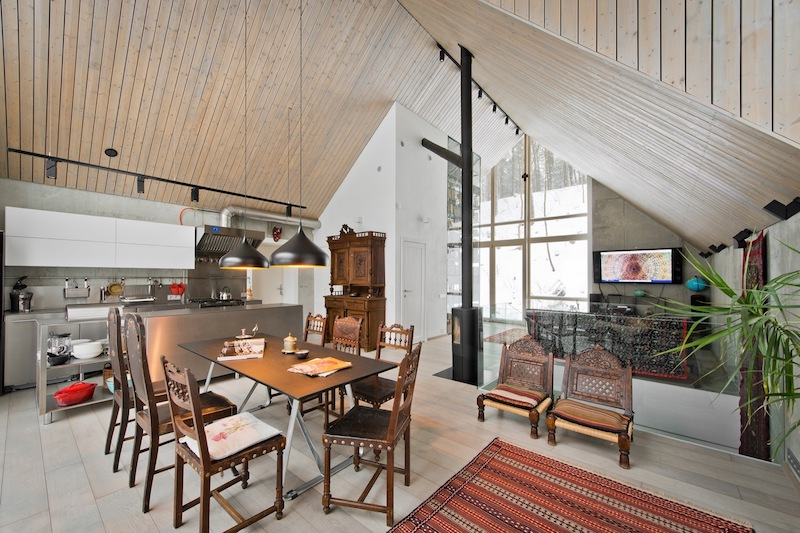 The kitchen is stainless steel and white, the dining space is done with carved wooden chairs that echo with the sideboard