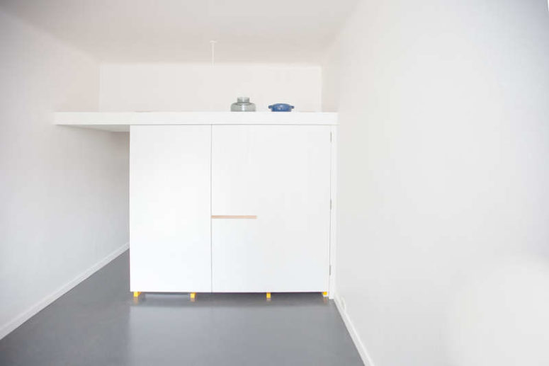 The kitchen piece can be completely closed with white doors to make it invisible in the interior and there's storage space on its top