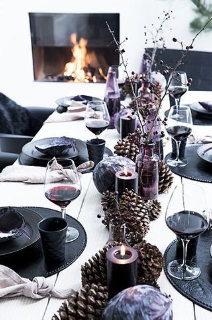 a black and purple New Year's table setting with oversized pinecones, purple candles and black chargers and plates