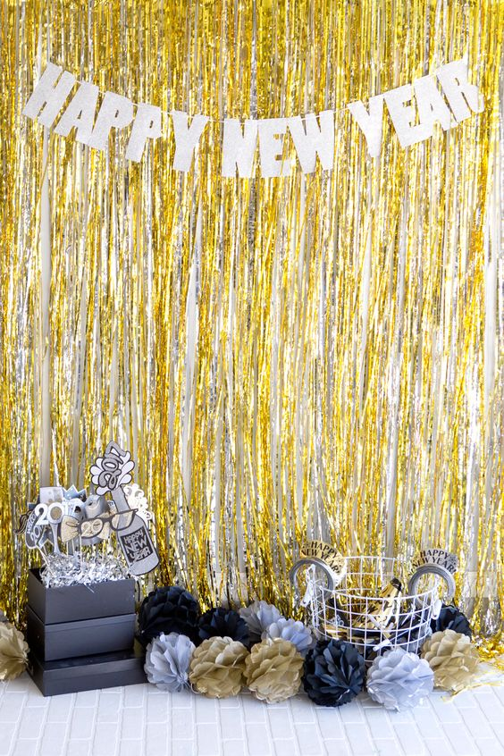 a bold photo booth in black, gold and silver with fringe and props