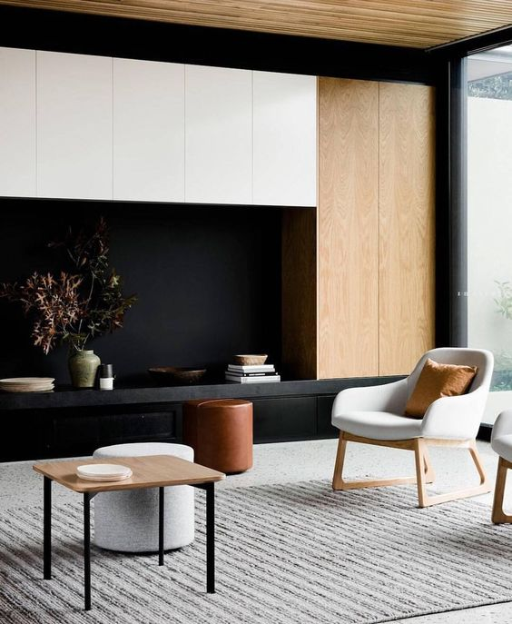 a contrasting living room with light colored wood, black and white furniture