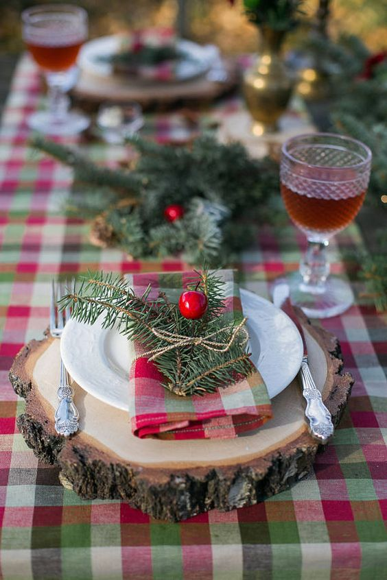 a plaid tablecloth, plaid napkins and evergreens with berries for a cozy rustic tablescape