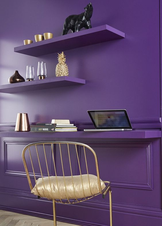 a violet statement wall with shelves and a floating desk