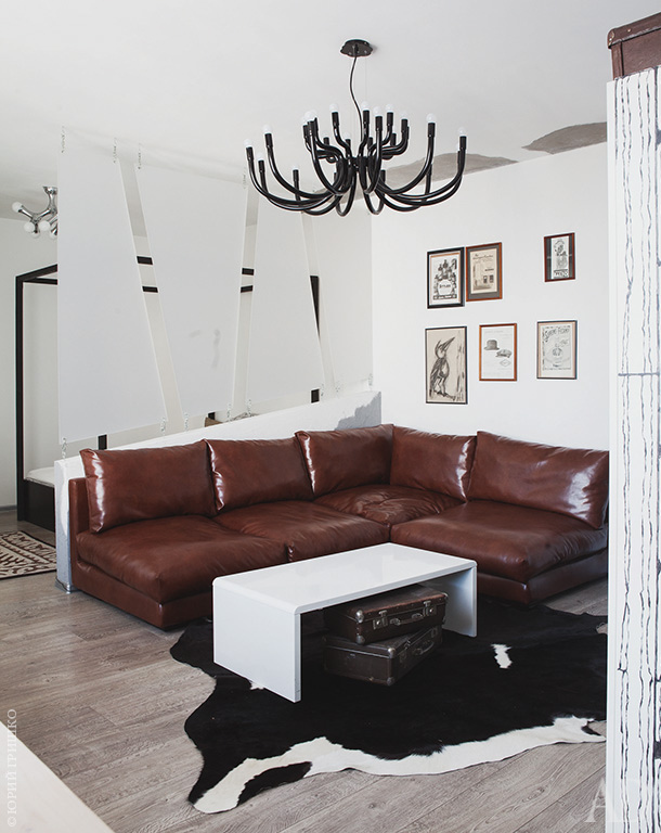 A faux animal skin rug adds coziness, and large black chandelier is inspired by antlers