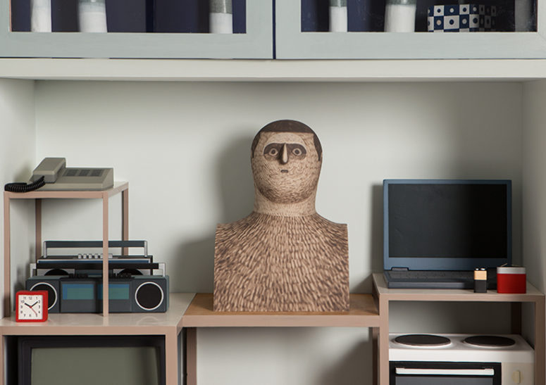 The bust of a man is surrounded by common objects that we used, all of them are fake