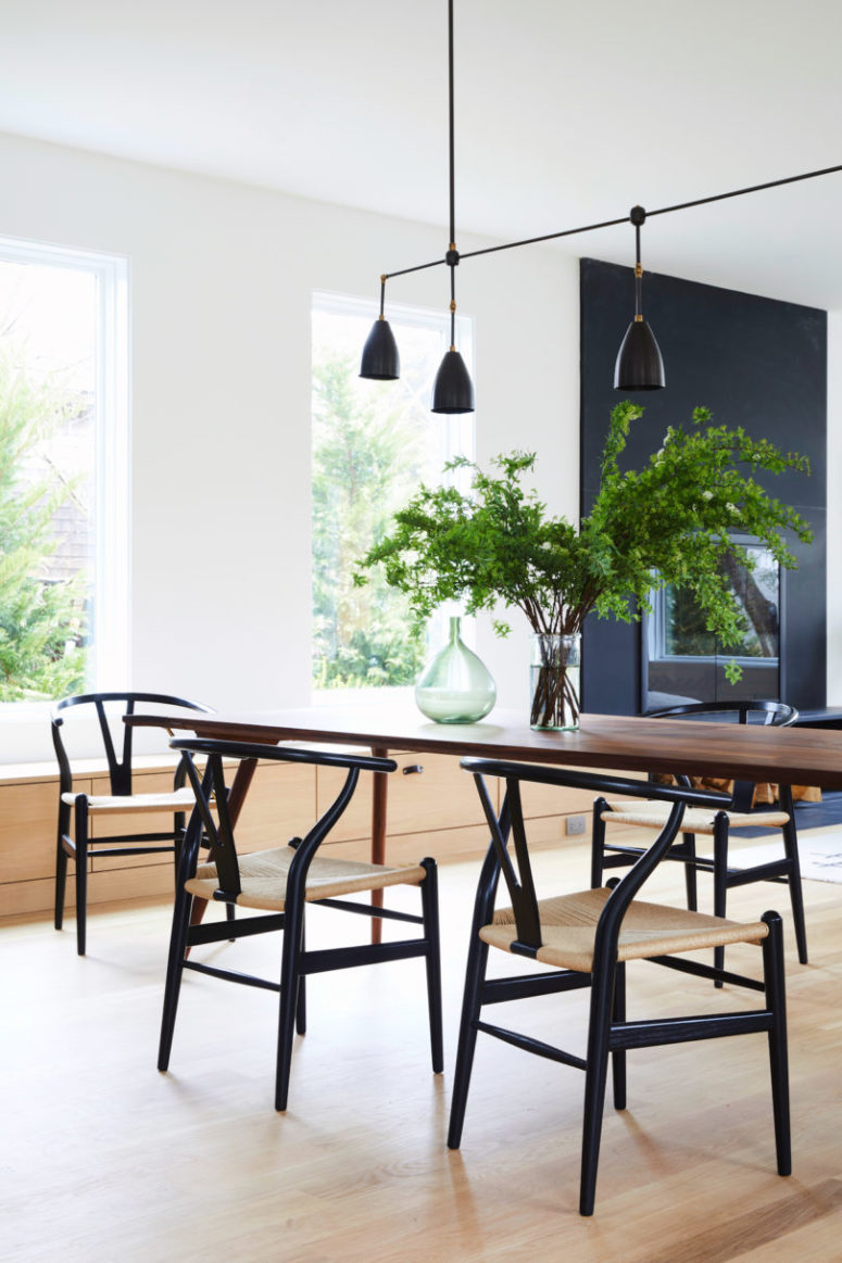 The dining space is done with a dining table and some eye-catchy bone chairs, black and brass lamps over the table mark the table