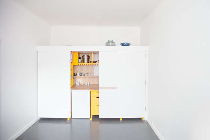 The kitchen design is done with light colored wood to contrast thesunny yellow cabinets