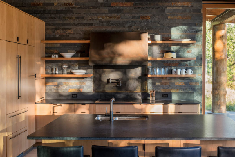 The kitchen is done with light colored wooden cabinets, darkened metal appliances and stone countertops, the walls are clad with reclaimed wood