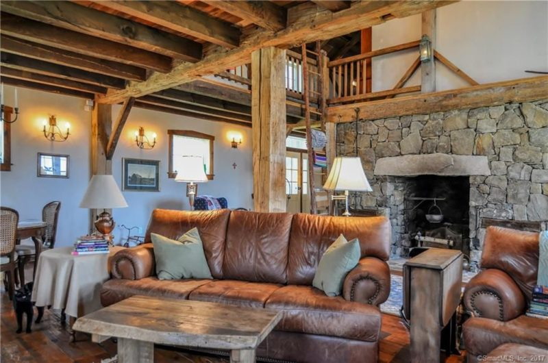 The living room features a selection of rustic and vintage furniture and a large fireplace with firewood storage