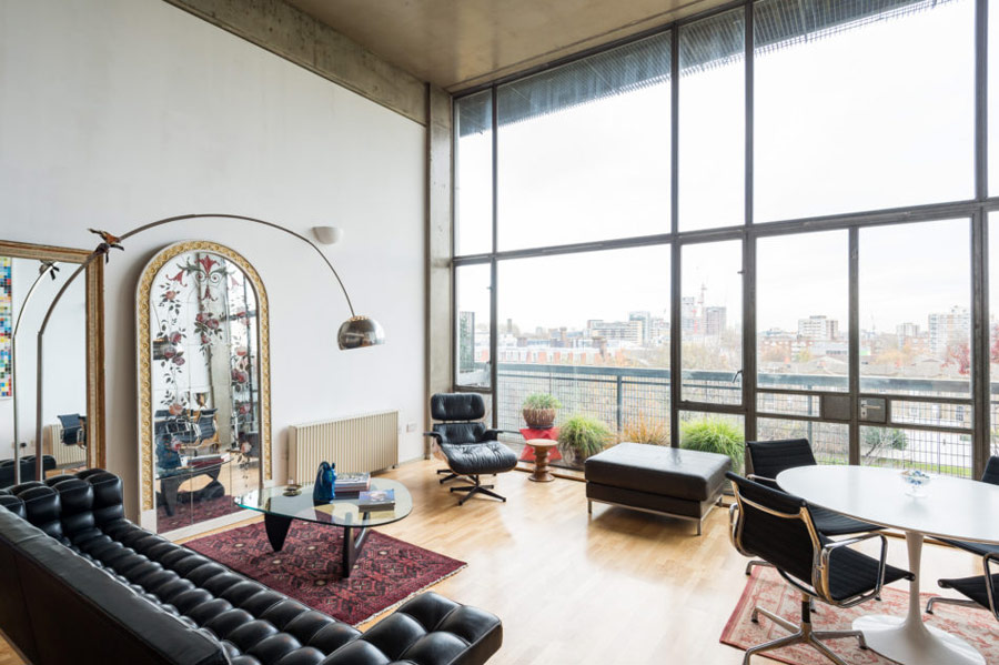 The living room is done with black leather furniture, several coffee tables and eye catchy vintage mirrors, it's flooded wit light through a glazed wall