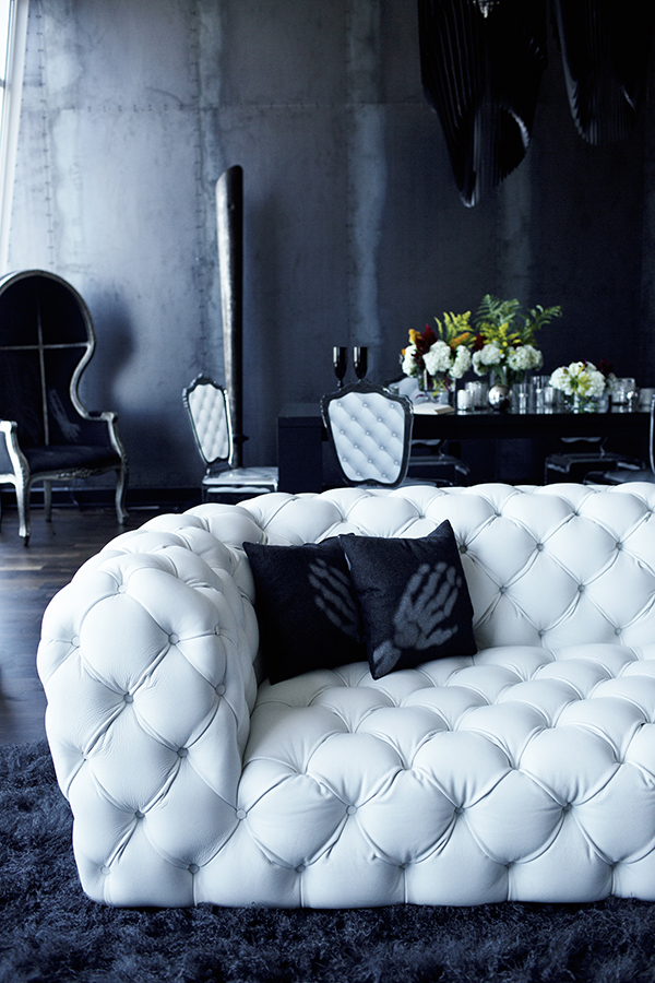 The space is done in black and very dark grey, with white upholstered furniture