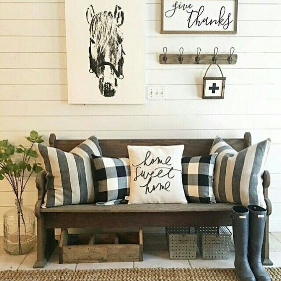 a barn-styled entryway with buffalo check pillows and calligraphy touches
