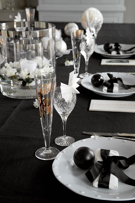 a black and white tablecape with floating flowers, a candle, black ornaments and white napkins