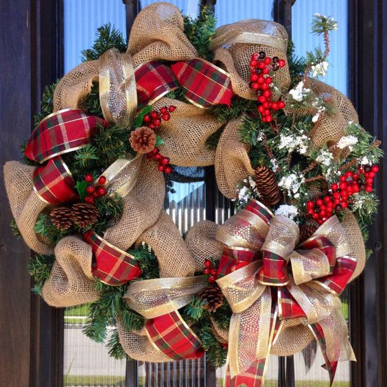 a burlap wreath with plaid and gold ribbon, pinecones, berries and evergreens for a Christmas door