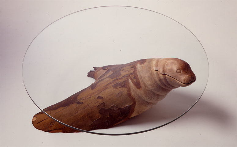 The Seal Table with a wooden seal and a glass tabletop