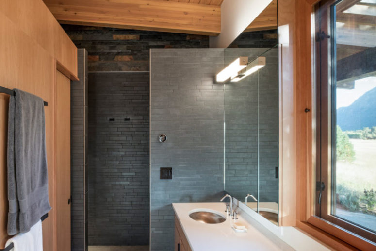 The bathroom is done with black stone and rich-colored wood, it's small yet very convenient