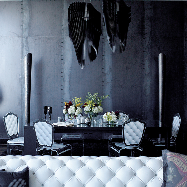 The dining space is defined with black sculptural chandeliers and metal pillars
