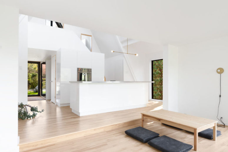The living room is united with a kitchen and the spaces are divided into two parts with a different floor level