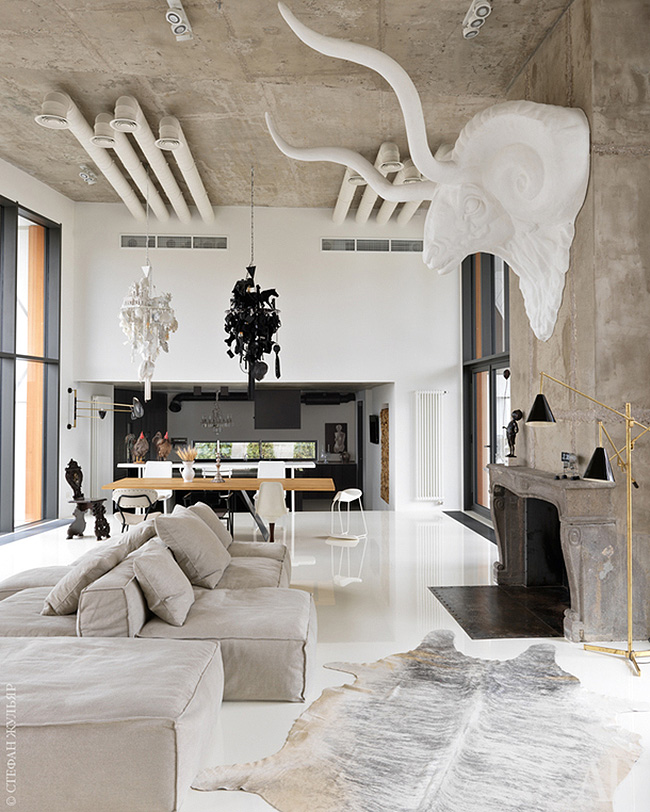 The living room is united with the dining space and kitchen and features an oversized animal head sculpture