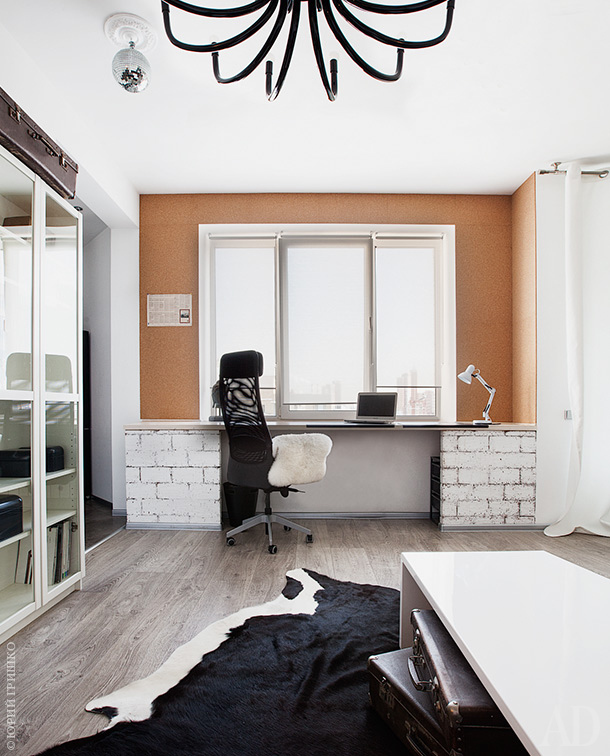 The working space is done with an orange wall, brick pillars, and it's filled with natural light