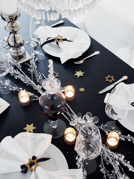 a black table decorated with gold stars, candles, silver branches and candles