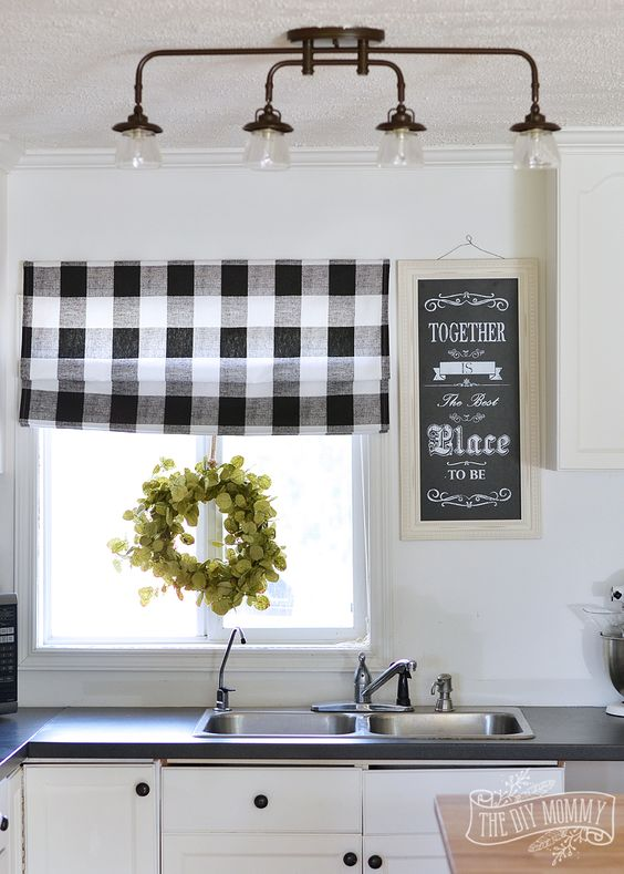a buffalo check roman shade, a greenery wreath and a chalkboard sign for a cozy barn-styled kitchen