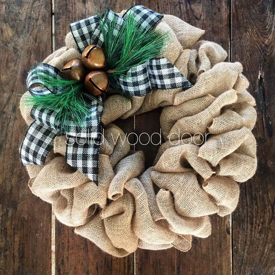 a burlap wreath with a buffalo check bow, jingle bells and faux pine needles