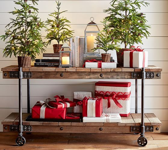 evergreen trees in baskets and gifts and candle lanterns for a festive feel