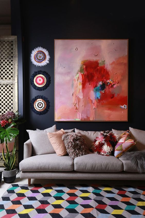 the artwork not only fits the space but also echoes with colorful pillows