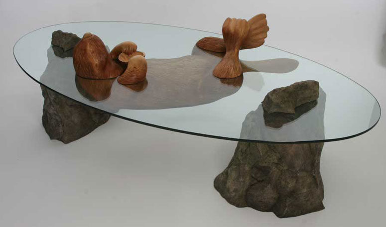 Sea Otter table features stones, a wooden otter and a glass tabletop