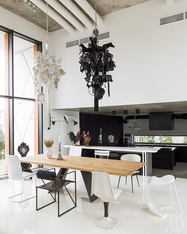 The dining space is done in black and white, with mismatching chairs and unique chandeliers