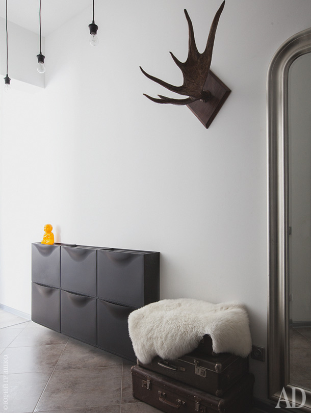 The entryway is done with vintage suitcases for storage, antlers and a black wall-mounted storage piece