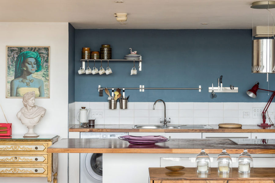 The kitchen features white cabinets with wooden countertops, a graphite grey wall and a white tile backsplash