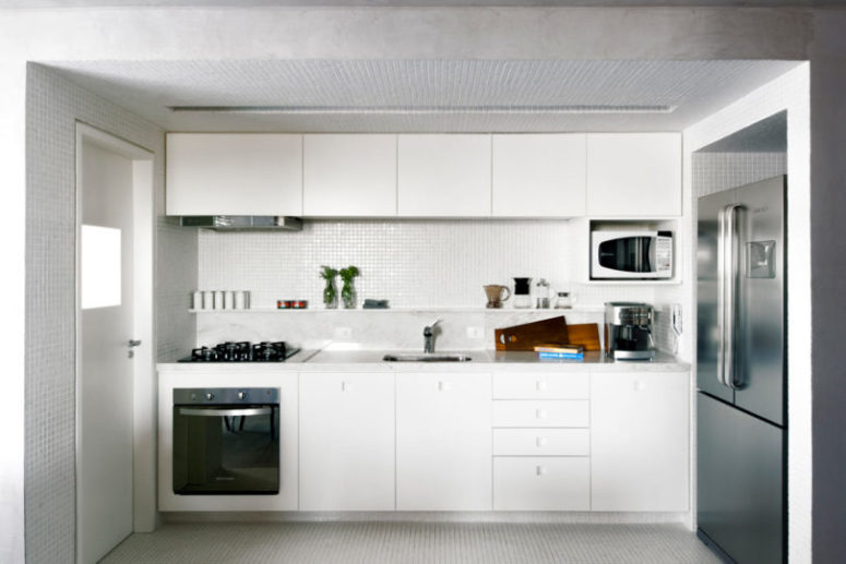 The kitchen is done in white, with a different floor and lower ceiling to visually separate it from the rest of the space