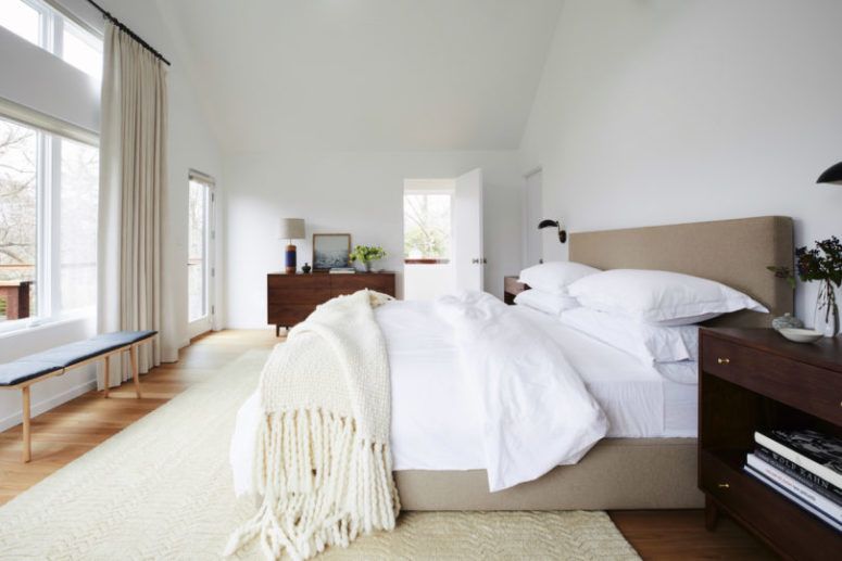 The master bedroom is decorated in neutral shades, with much natural light and several dark-colored wooden pieces