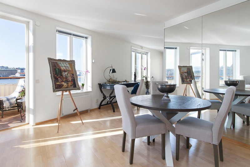 There's a large mirror that accentuates the river views and a dining zone with a round wooden table