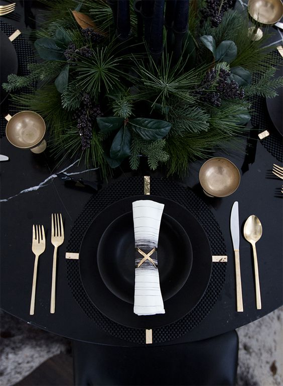 a black table with black plates and cahrgers, lsuh evergreens and gold cutlery for a moody tablescape