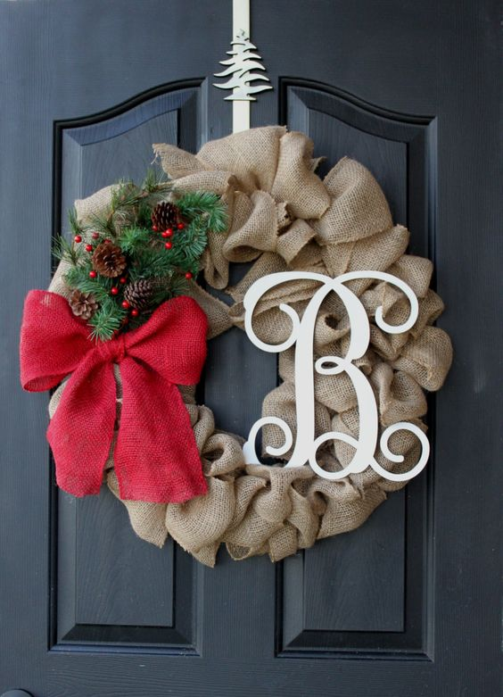 a burlap wreath with a monogram, a red bow and evergreens and pinecones for a chic look