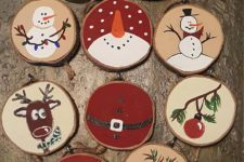 05 various painted wood slice ornaments that include snowmen, stockings, deer and trees