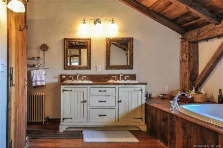 The bathroom is clad with wood, even the bathtub and there's a vintage vanity