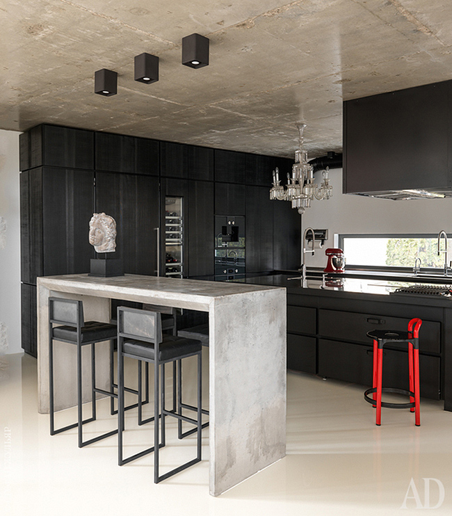 The kitchen is black, in wood and metal, with a crystal chandelier, a concrete console table and some stools
