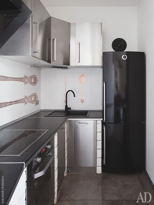 The small kitchen is done with stainless steel cabinets, a black fridge and a tile backsplash