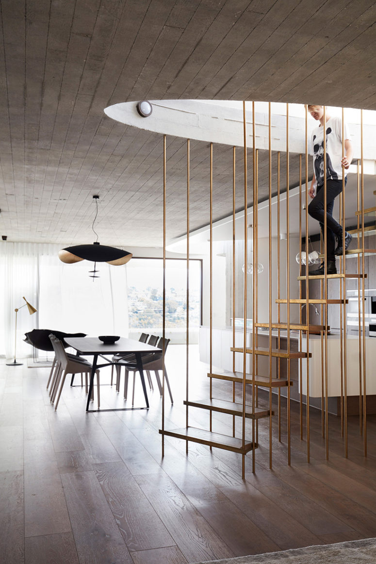 The stair is a concrete and brass piece, which connects all the levels of the house