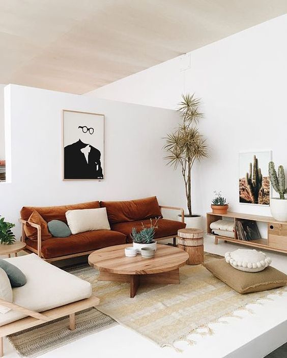 a Japandi living room with whites and light-colored wooden furniture, cognac textiles and sades of green for a cool look