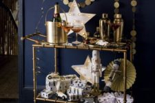 06 a brass bar cart with a gold garland, a neon star sign, paper fans and a balloon