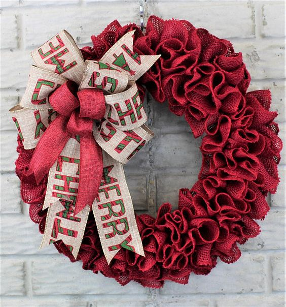 a red burlap wreath with large bows with letters looks bold and festive