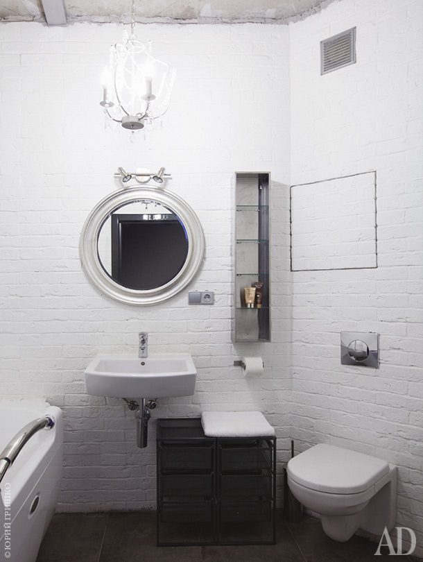 The bathroom is done with faux brick walls, some white appliances and a glass shelf on the wall