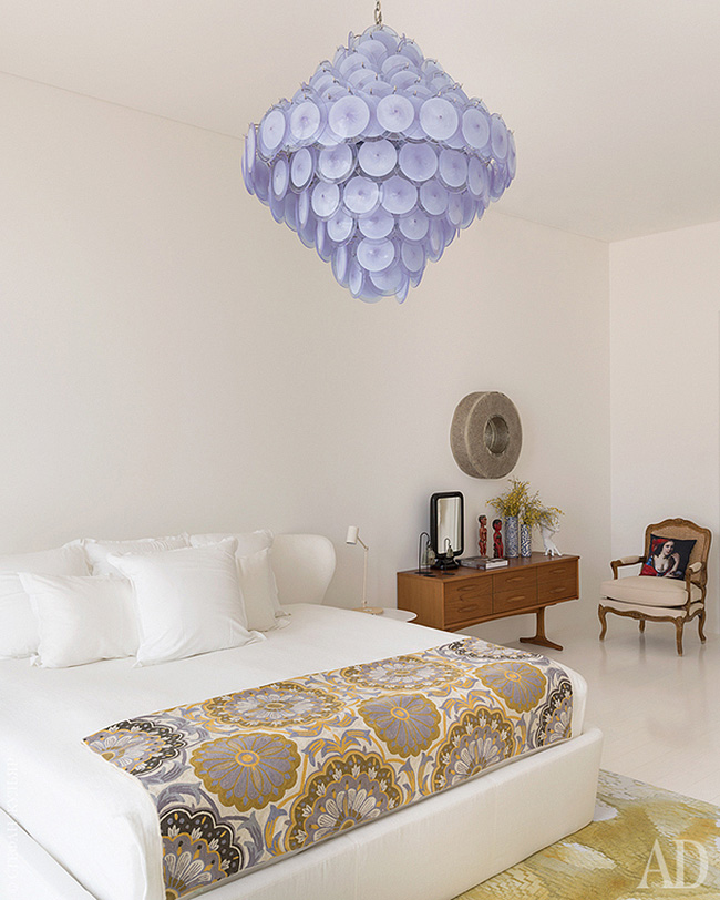 The master bedroom is done with an upholstered bed, a lavender disc chandelier and some vintage furniture